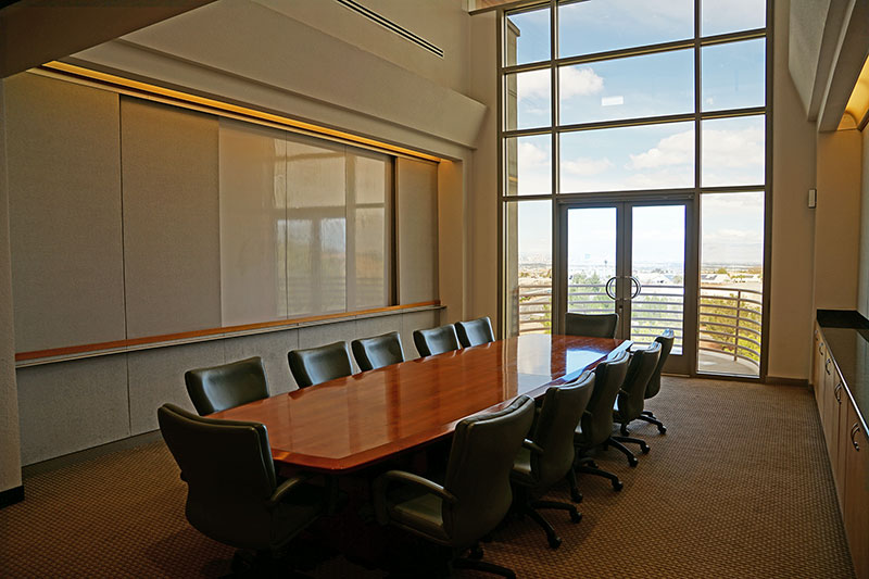 A large meeting room with a conference table, chairs, and a whiteboard