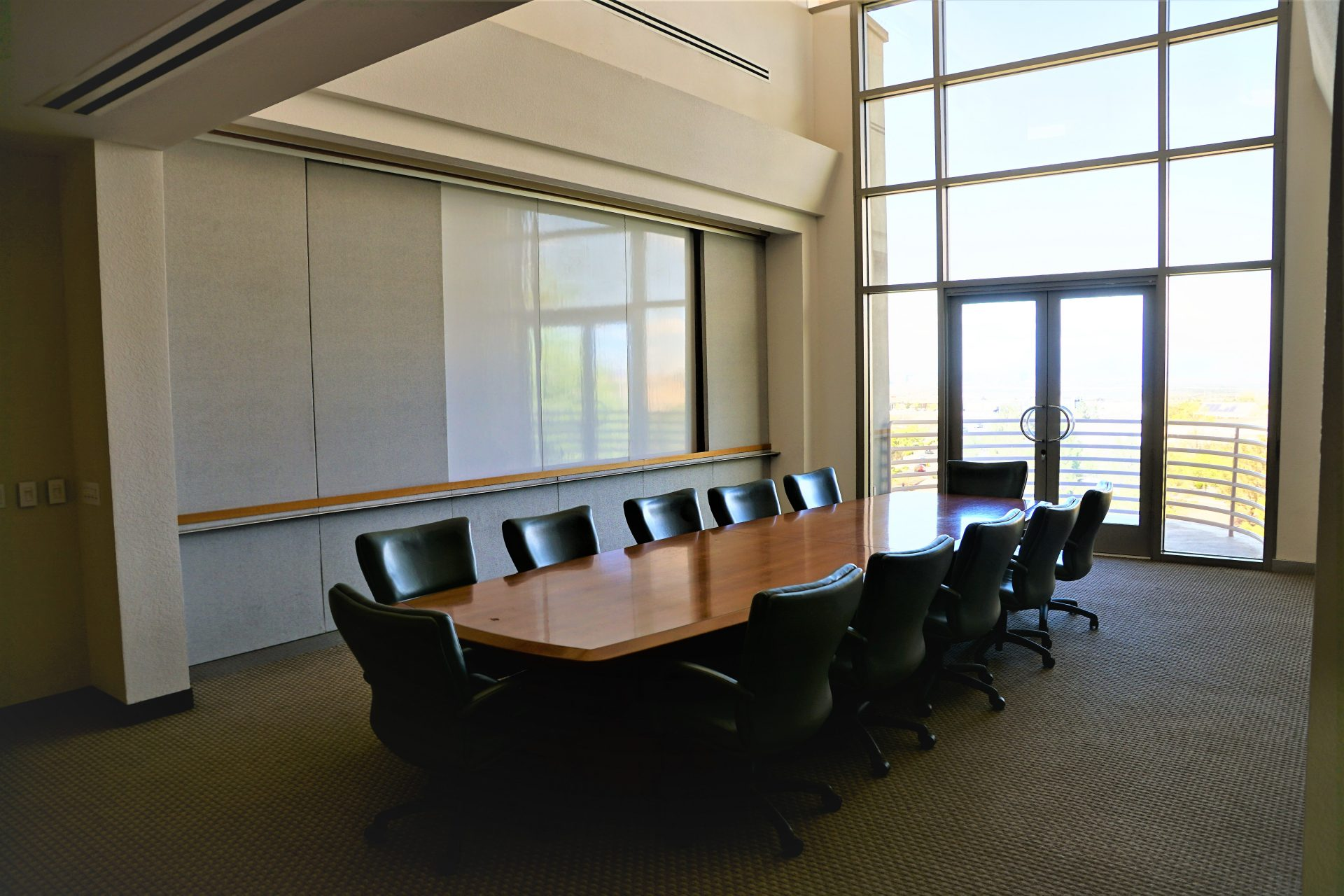 Boardroom with lots of windows, a conference table, and a white board